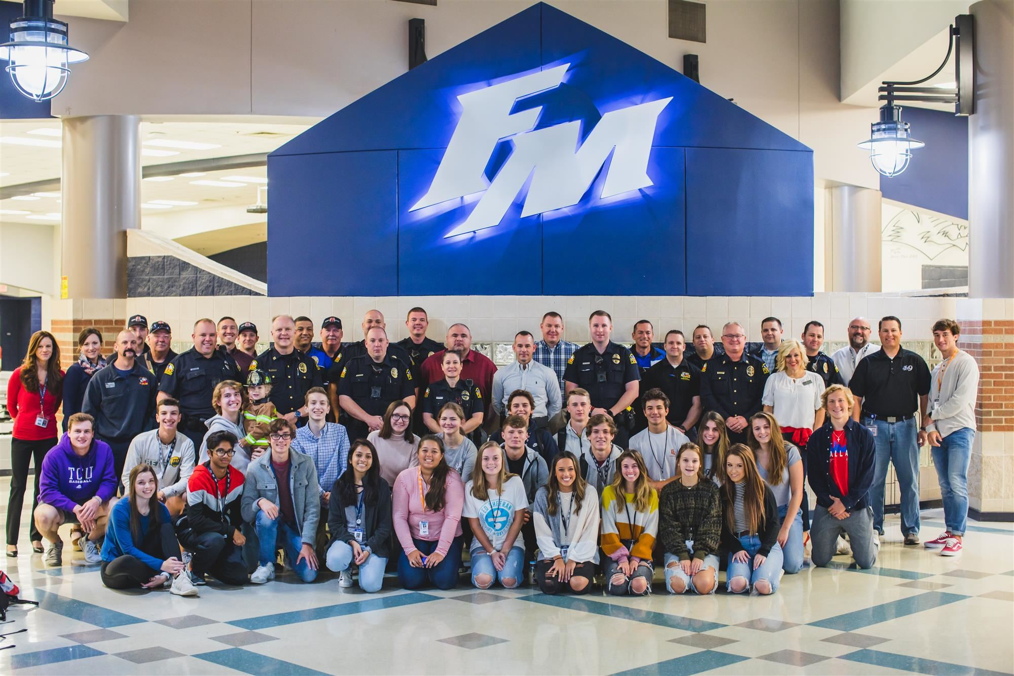 Group picture of Flower Mound police and firefighters standing with FMHS students. 2019