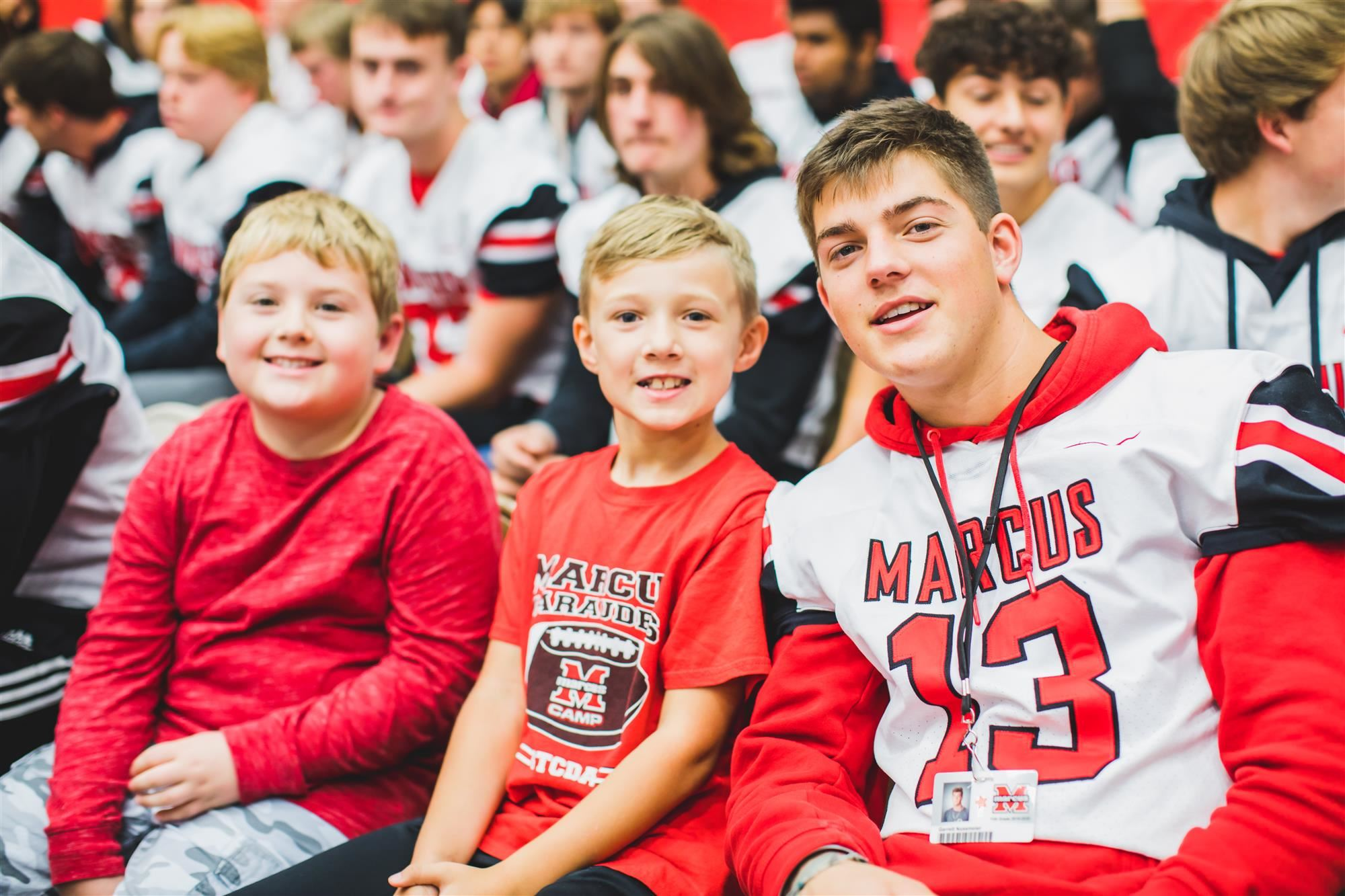Flower Mound Elementary students sit with MHS football player during the pep rally. 2019