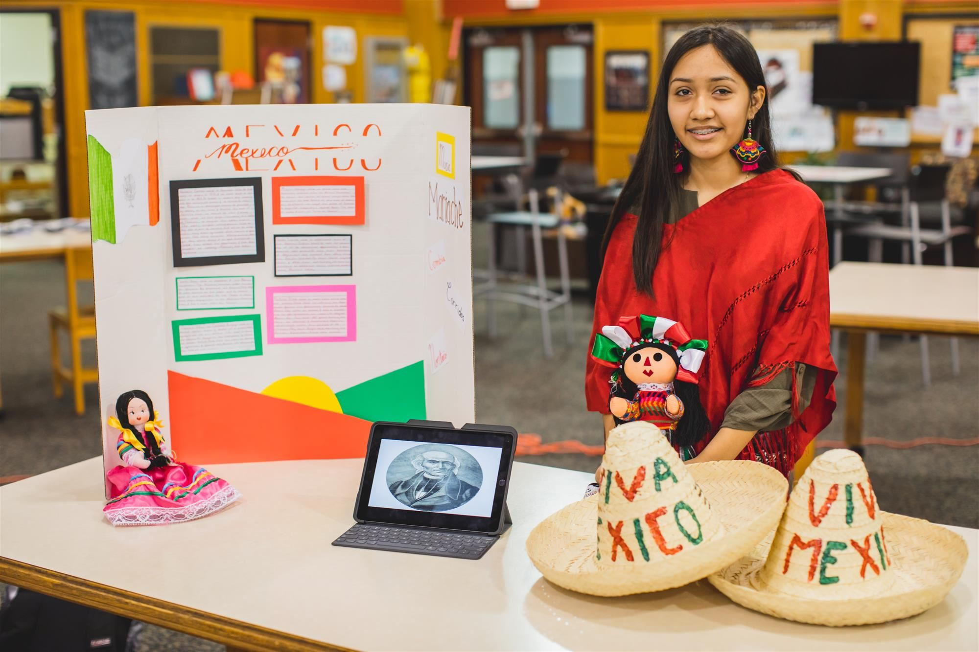 MHS student poses at her booth about Mexico for Celebrate Marcus! 2019