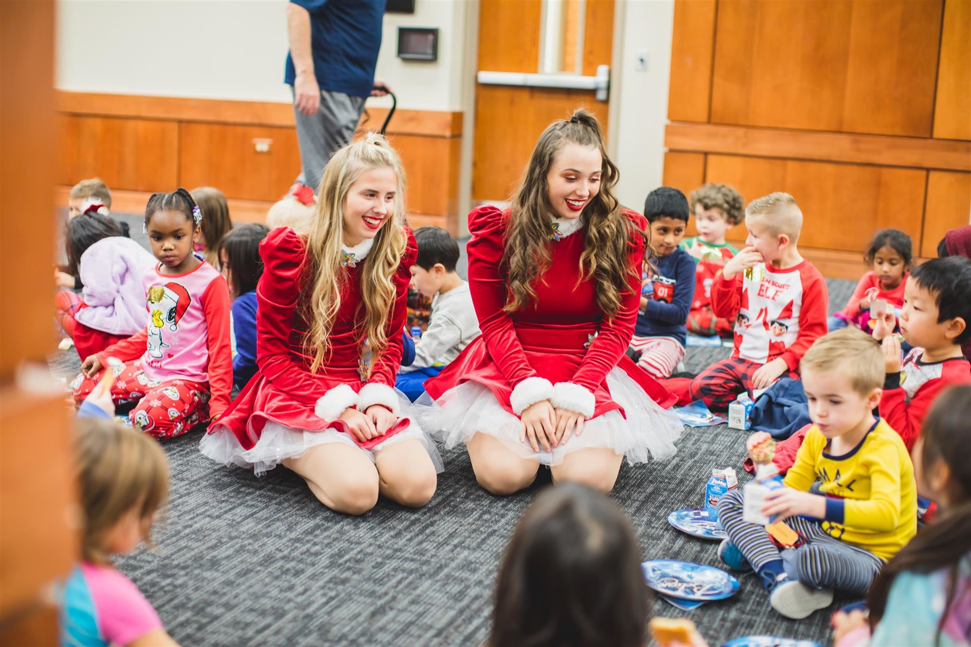 Flower Mound High School Drill Team members talk with Forest Vista Elementary Kindergartners while they eat their cookies.