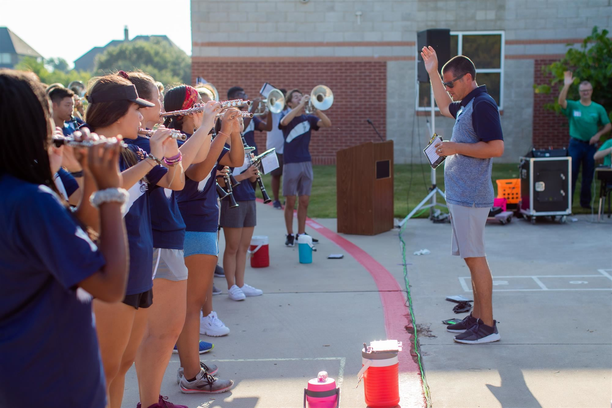 Flower Mound High School Band Director leads band in Flower Mound High School song.
