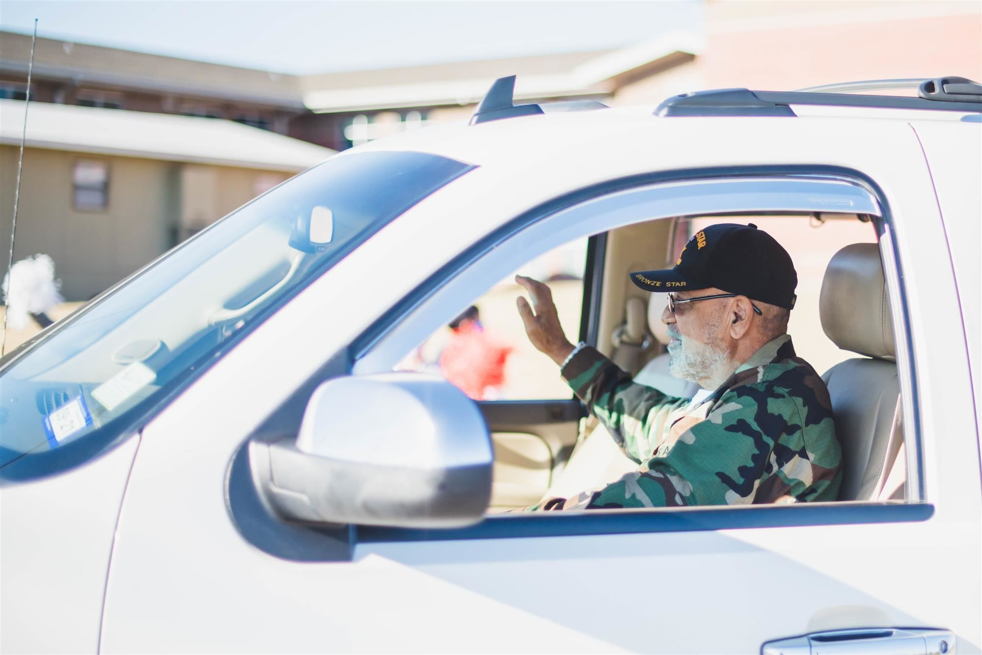 Veterans waves from vehicle during drive-thru parade.
