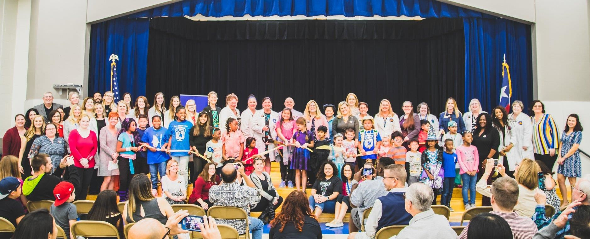 Polser Elementary Principal Lisa Phelps poses with students and staff before cutting the STEM Academies official ribbon. 2019
