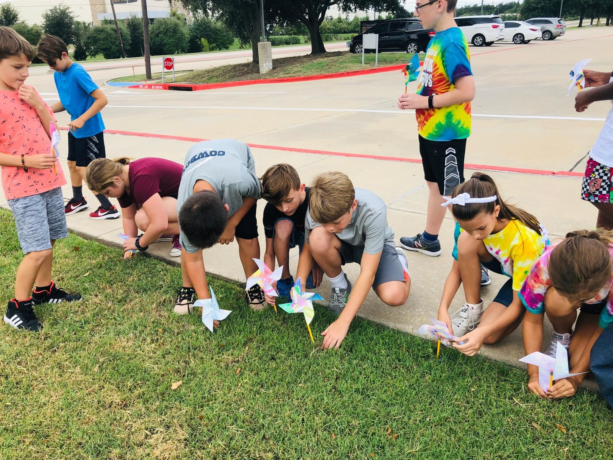 Bluebonnet students place their pinwheels in the grass outside school for world peace. 2019