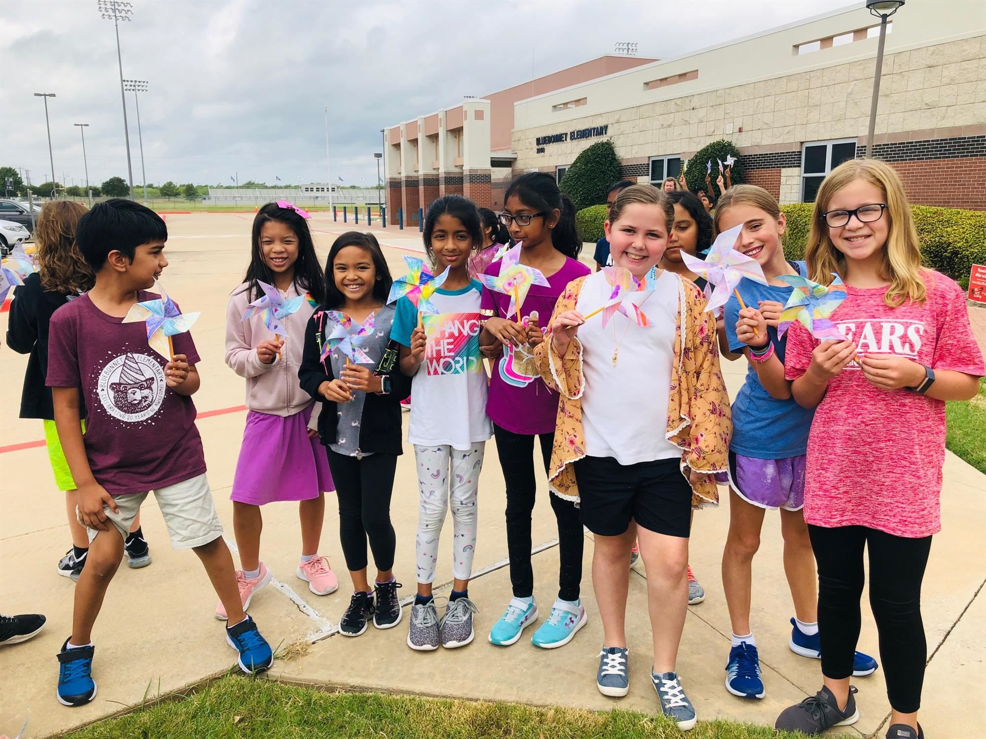 Bluebonnet elementary students pose with their pinwheels for peace outside of school. 2019