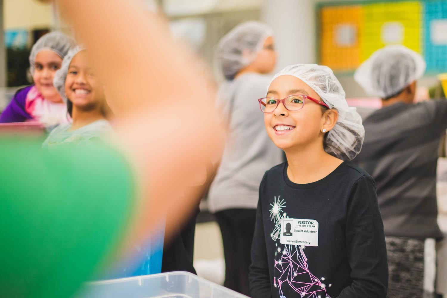 Students smile in hairnets