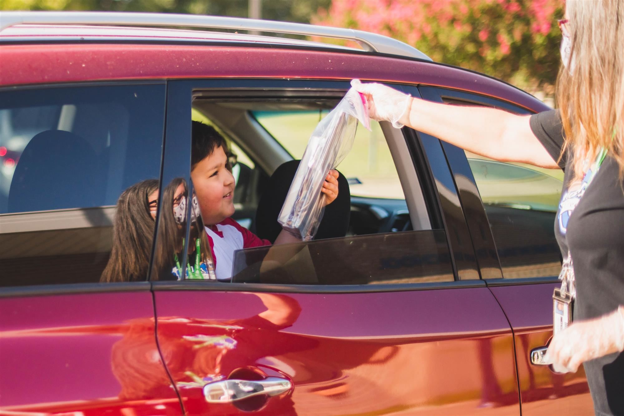 creekside student takes books at curbside pickup