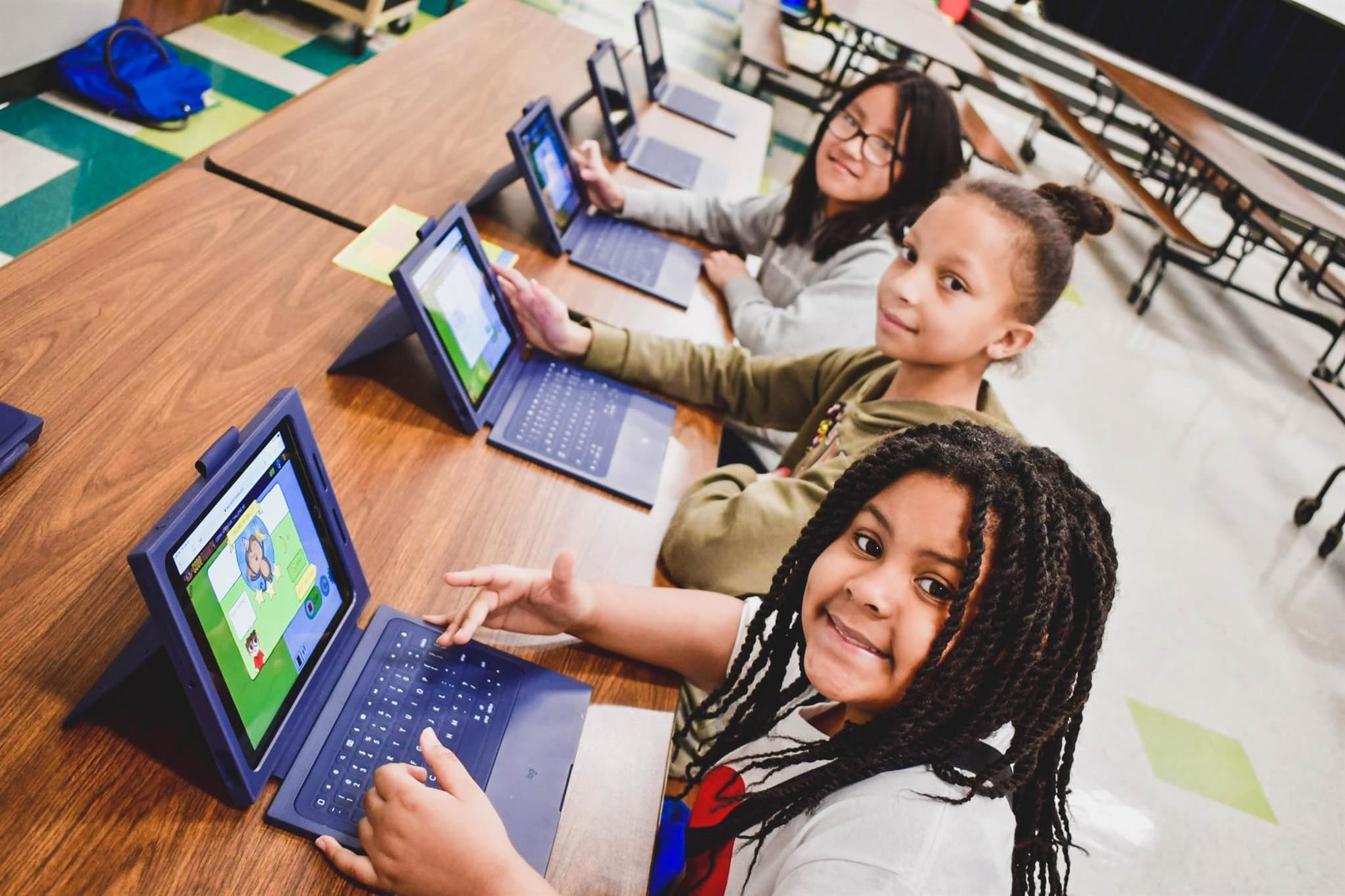 Students smile at tablet games