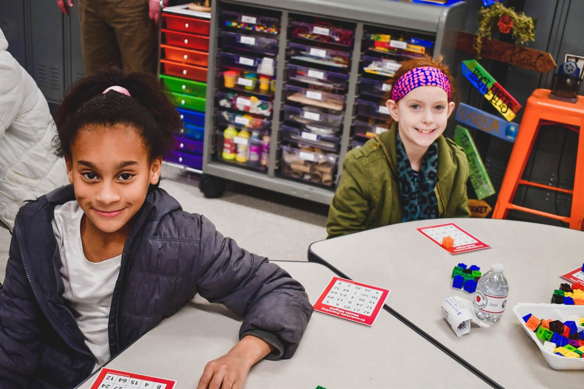 Two students smile with BINGO cards