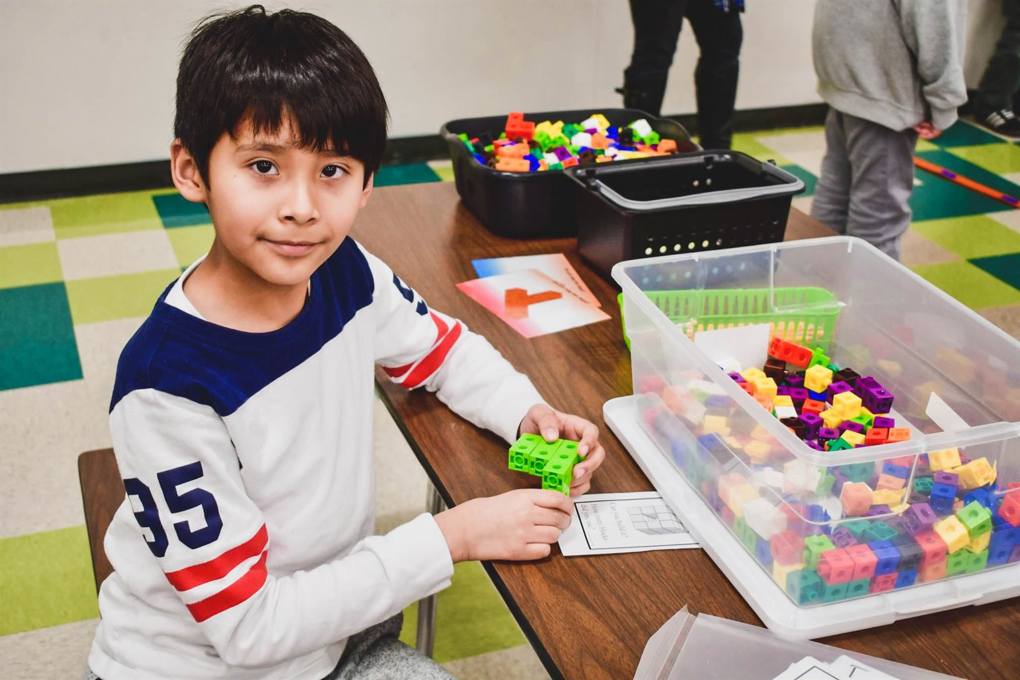 Student smiles with stem blocks