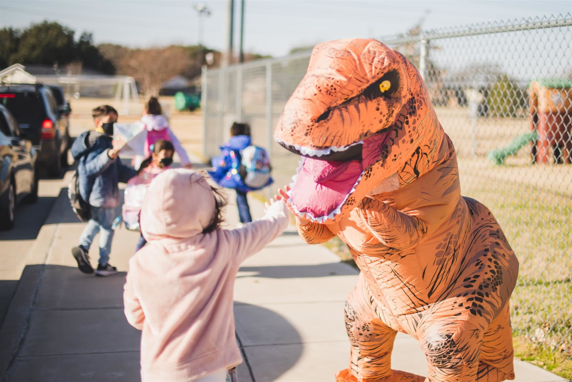 Educator in dinosaur costume waves to student