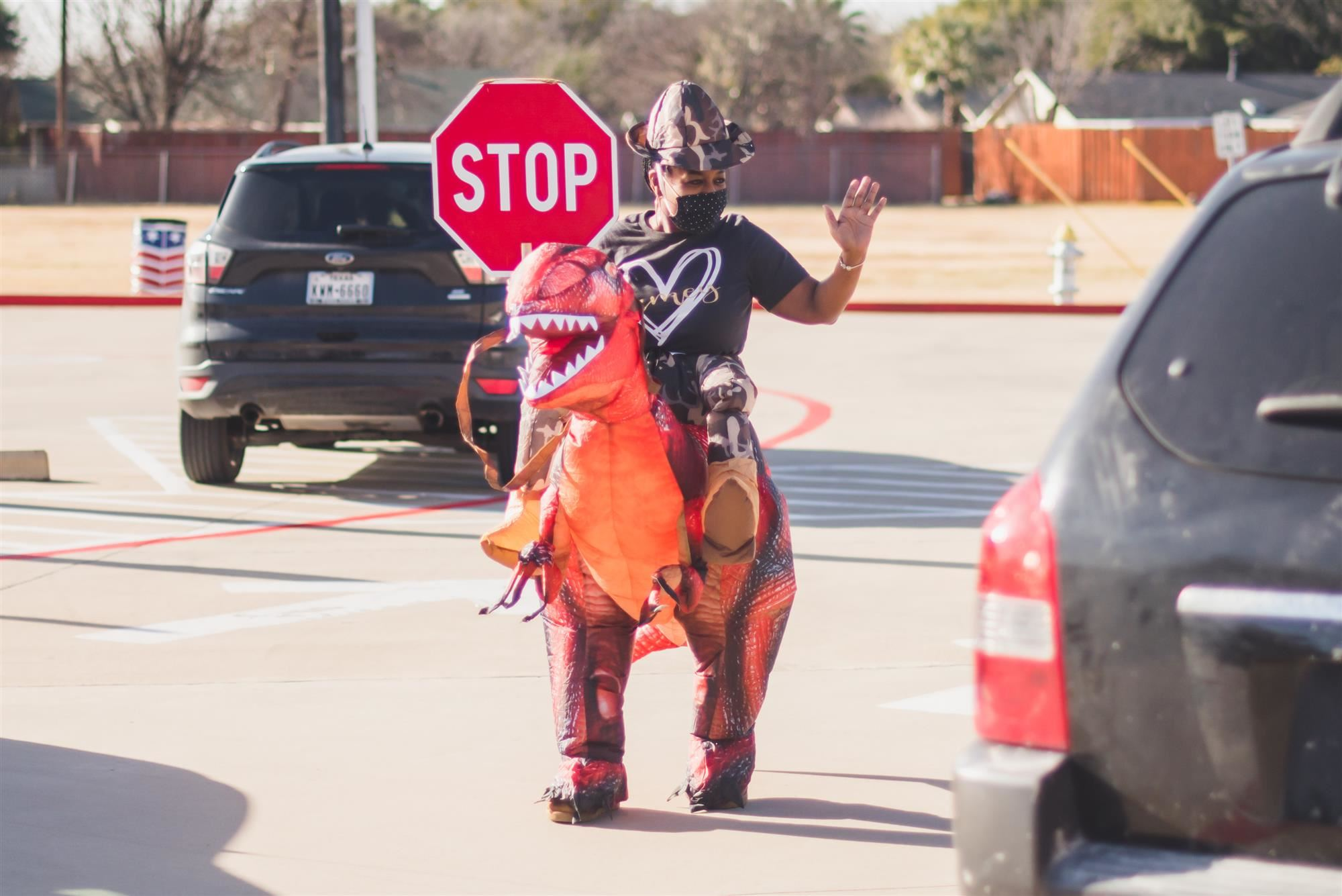 Educator wearing a dinosaur costume, holds stop sign and waves to cars