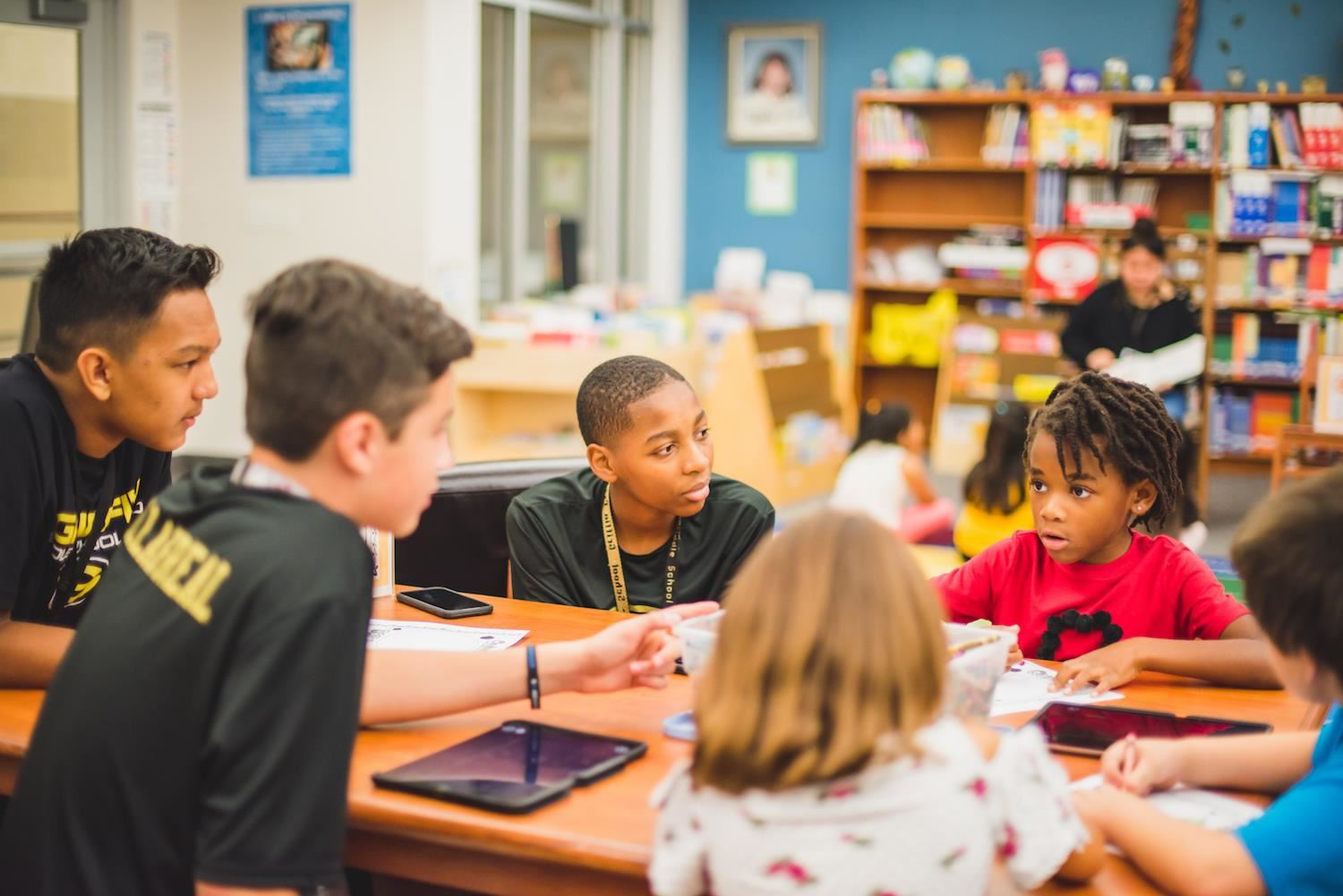 middle school students talk with younger, elementary student in library