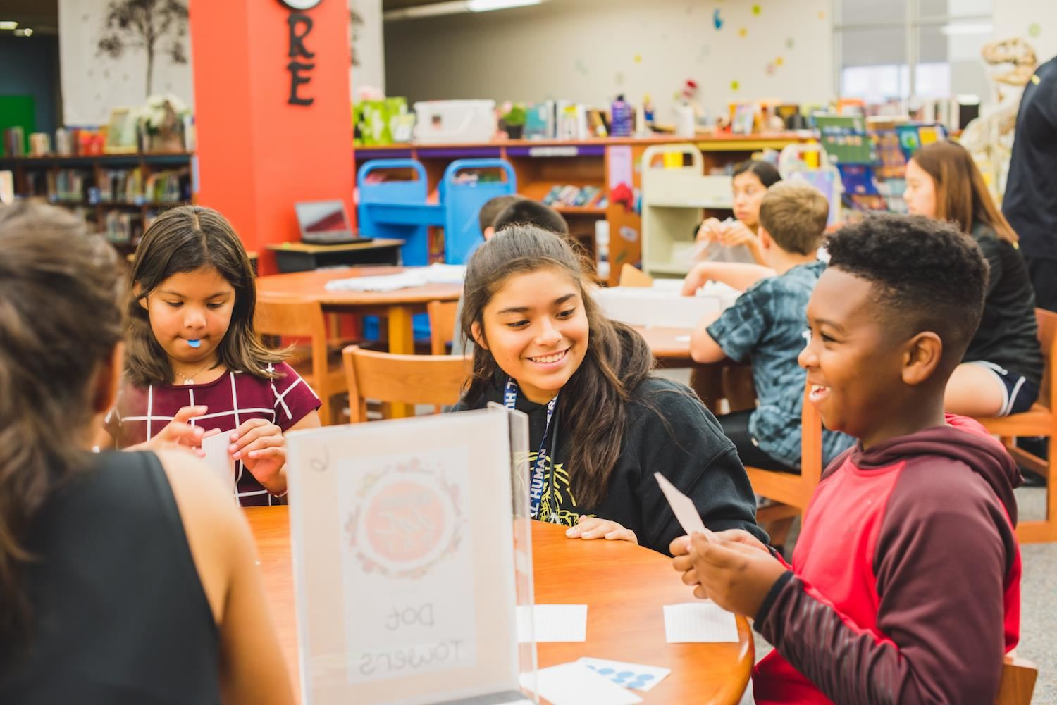 Middle and elementary students laugh at a library table