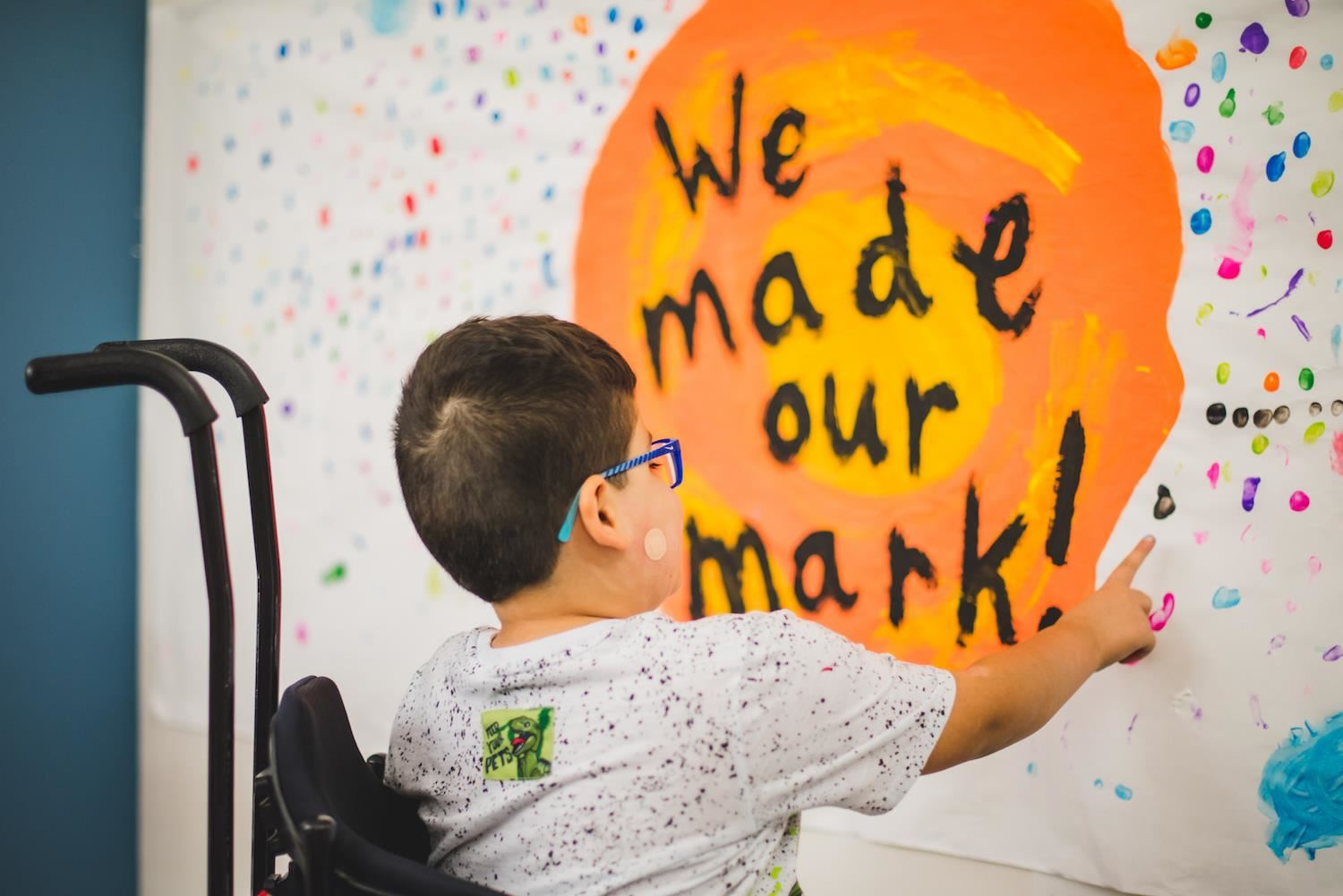 "students add paint dot to ""We made our mark"" sign."