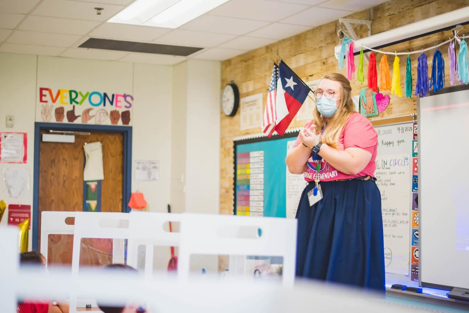 Teacher stands in front of colorful classroom