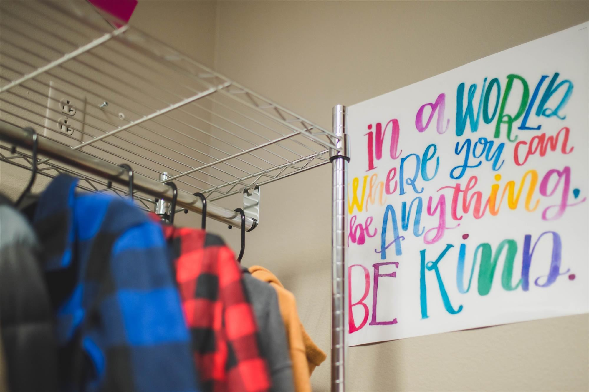 "coats hang near a poster that reads ""in a world where you can be anything, be kind."""
