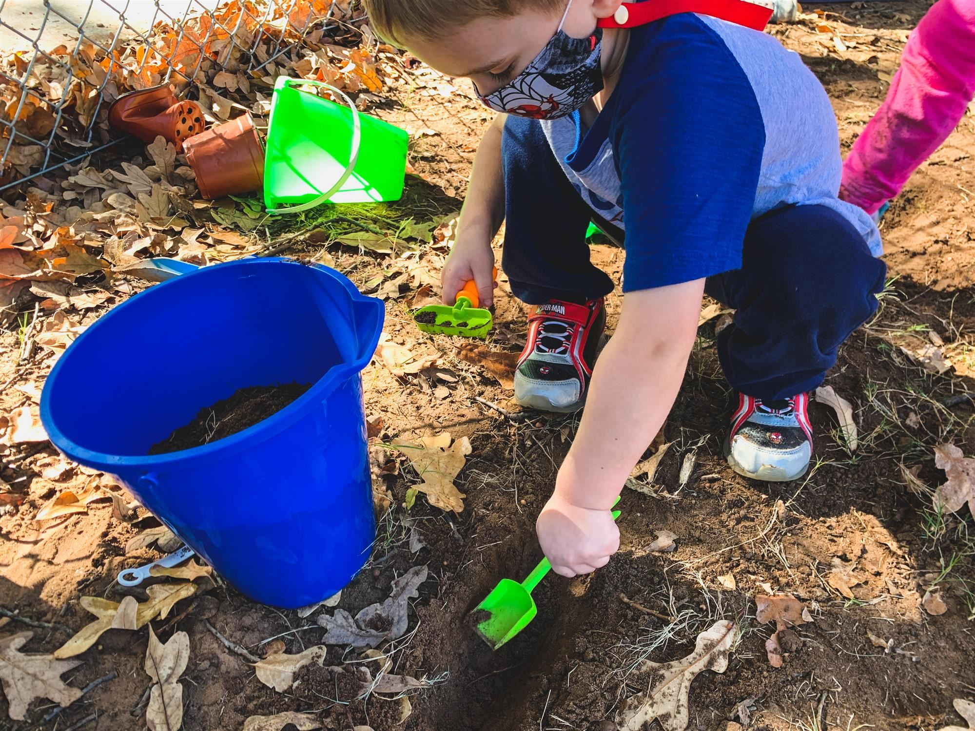student digs in dirt with shovel