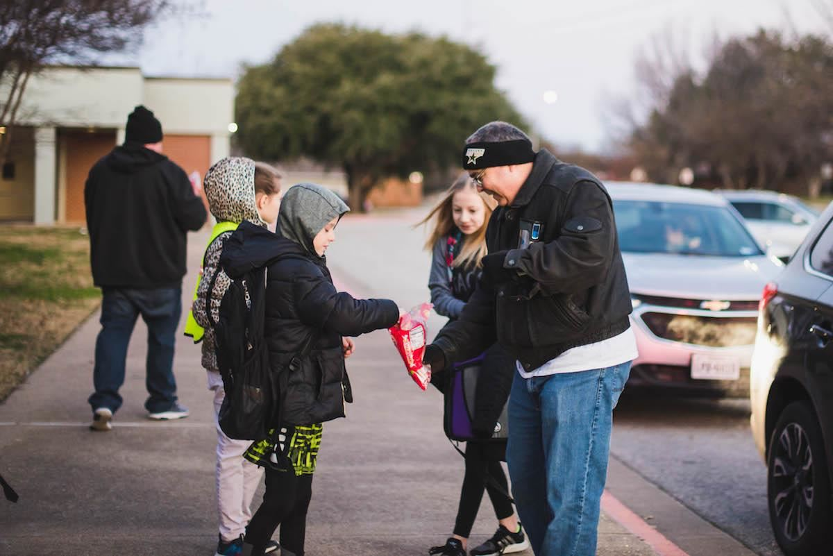 Watch DOGS pass out candy outside school