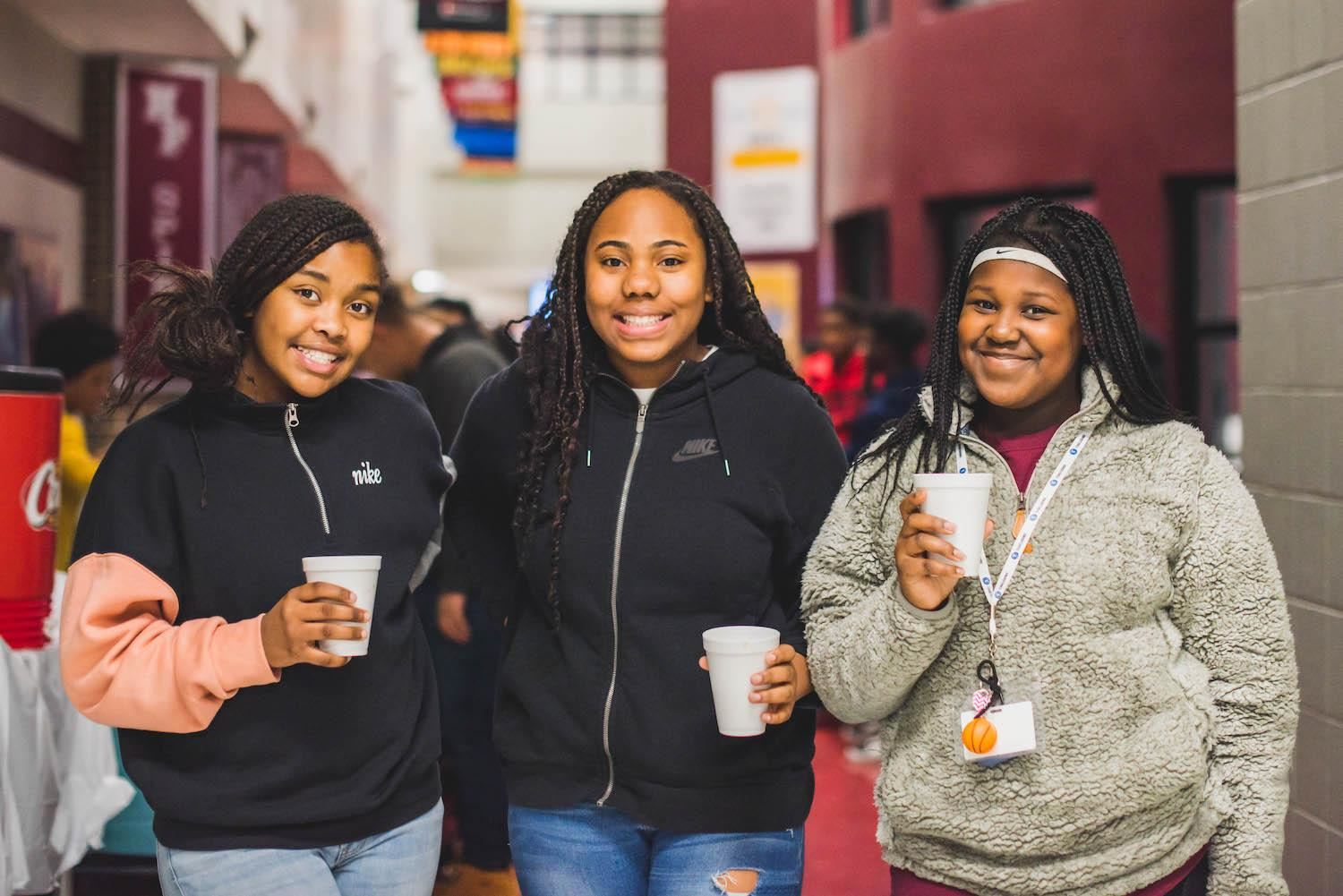 Three students smile at Black History Month celebration
