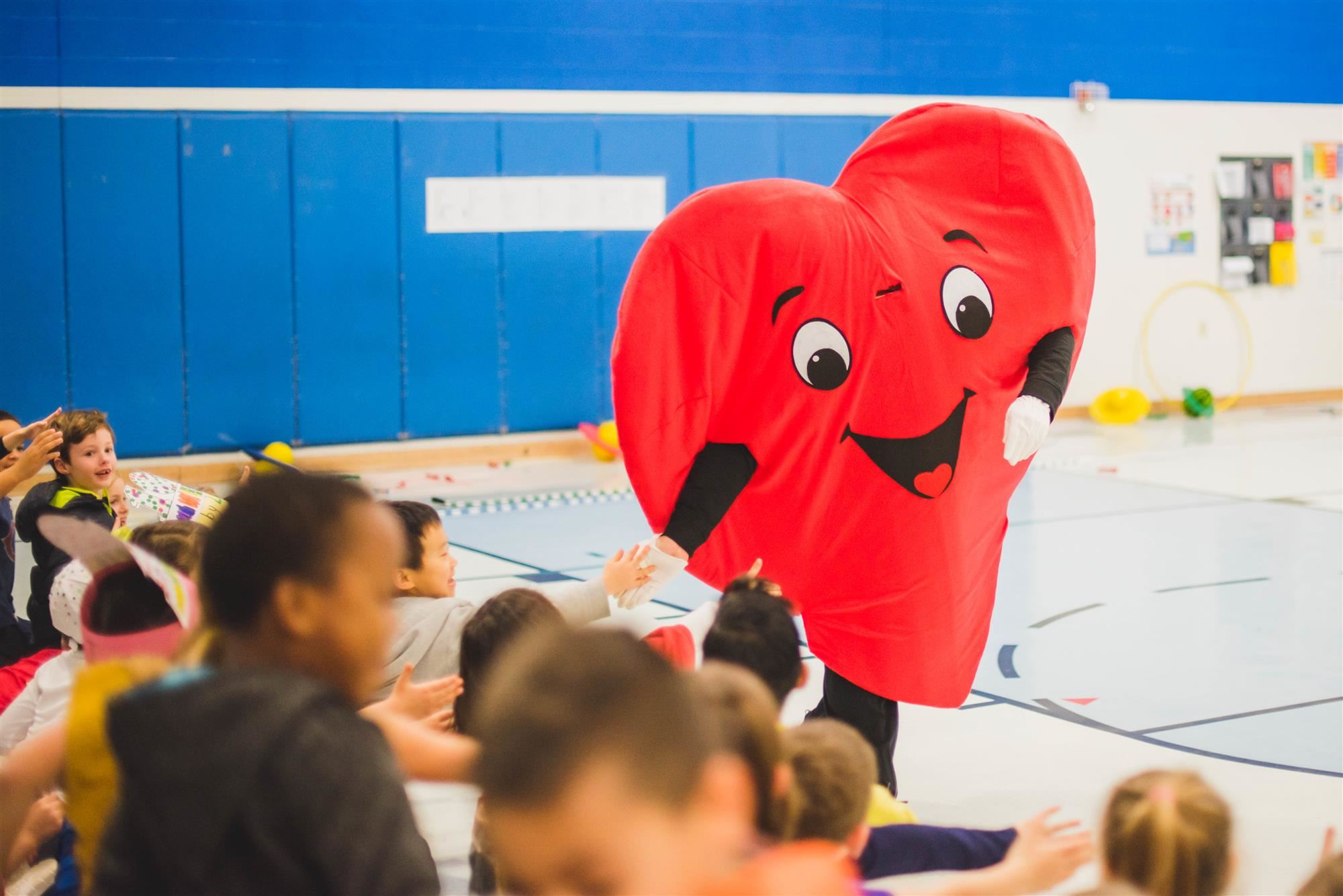 heart mascot greets students with high fives