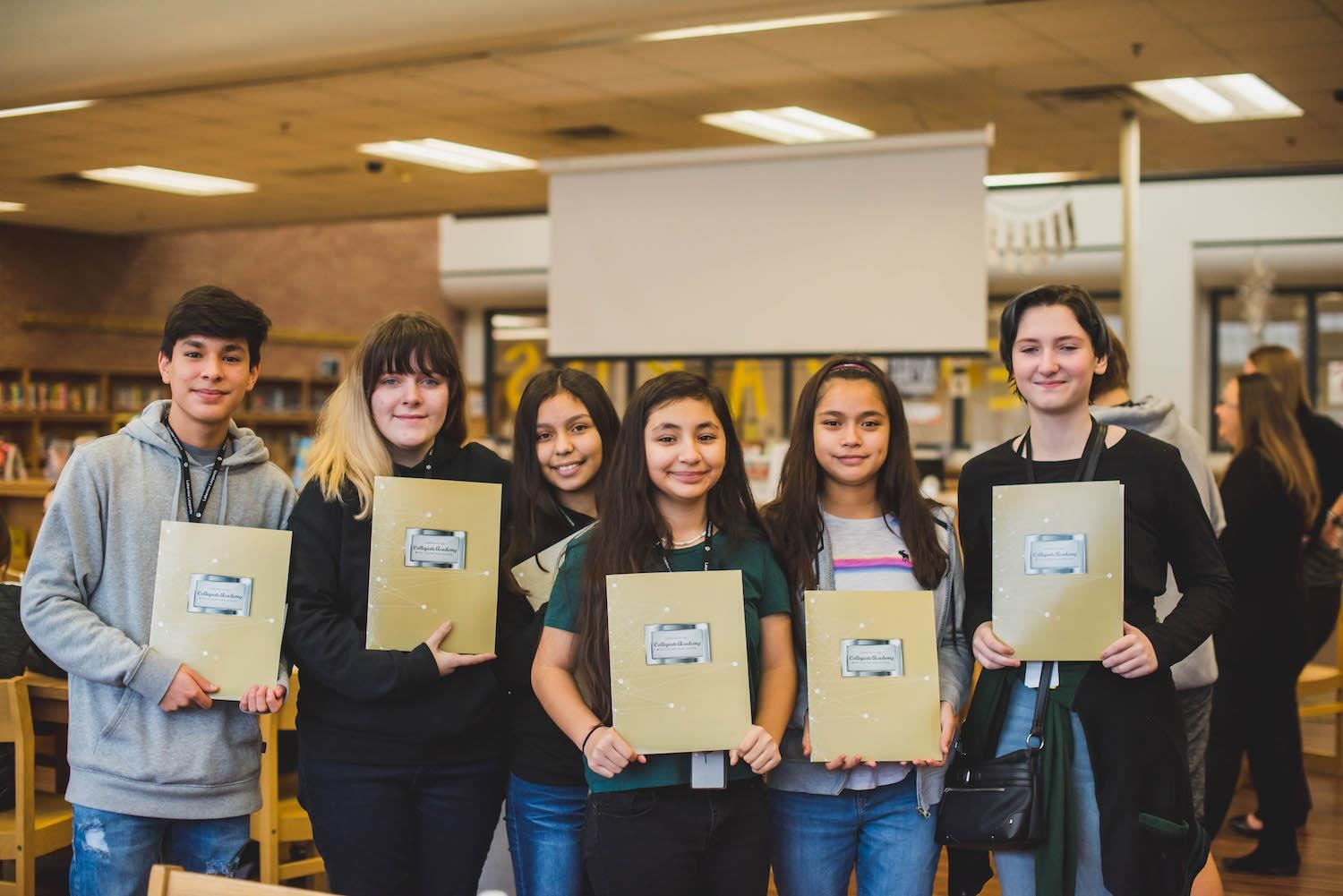 Students smile with collegiate academy folders