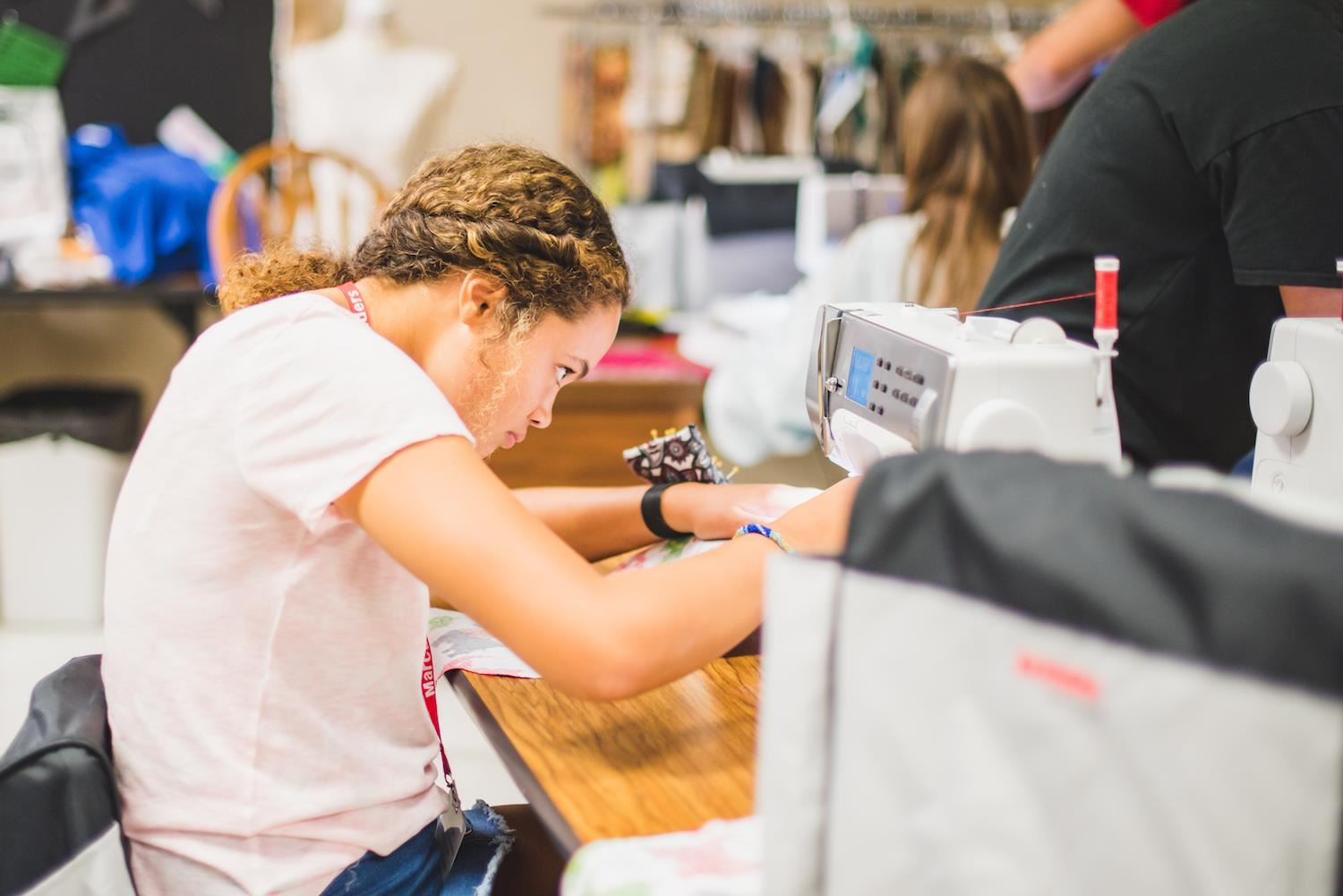 Student sews stocking with sewing machine