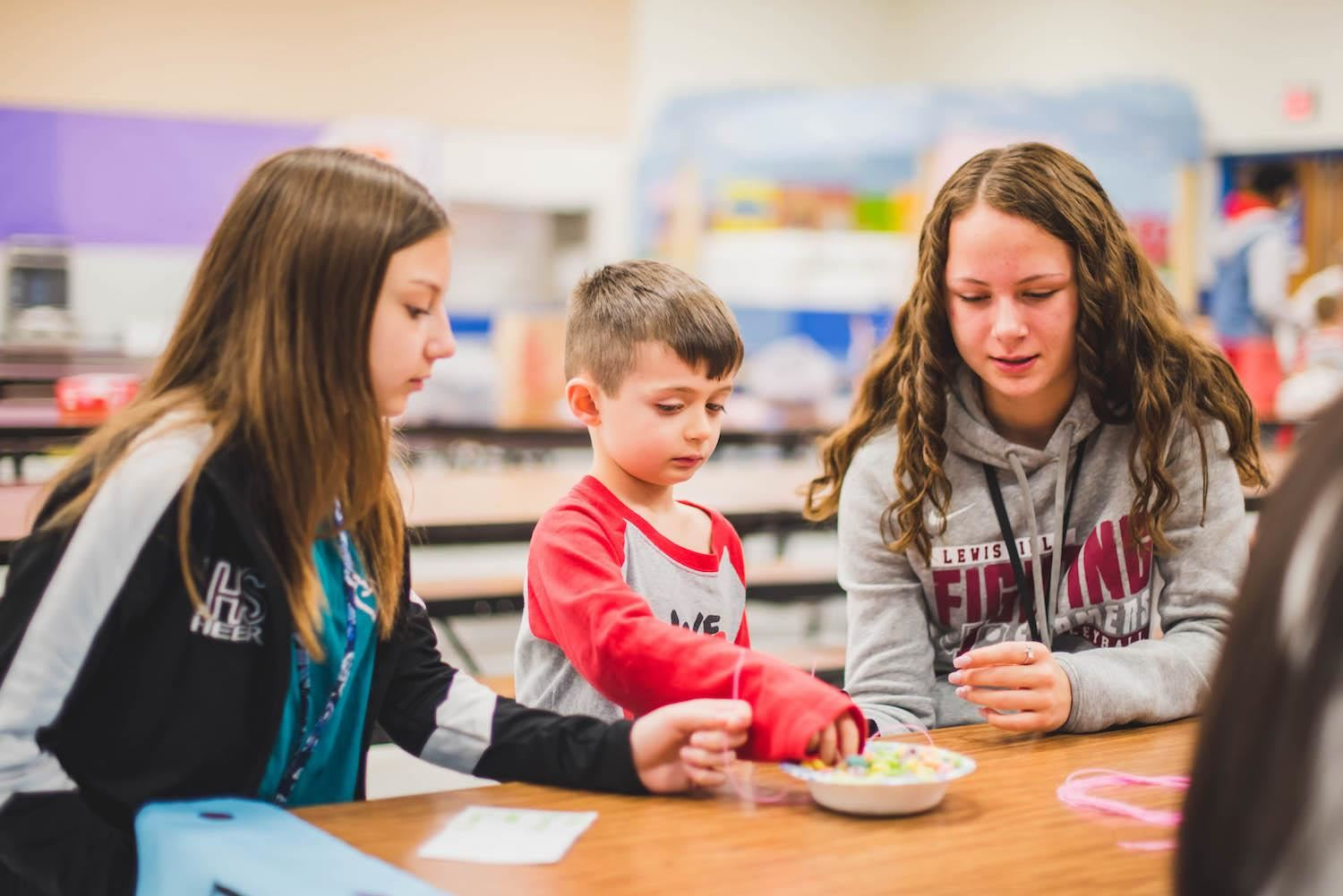 two older students help younger student string cereal onto necklace.