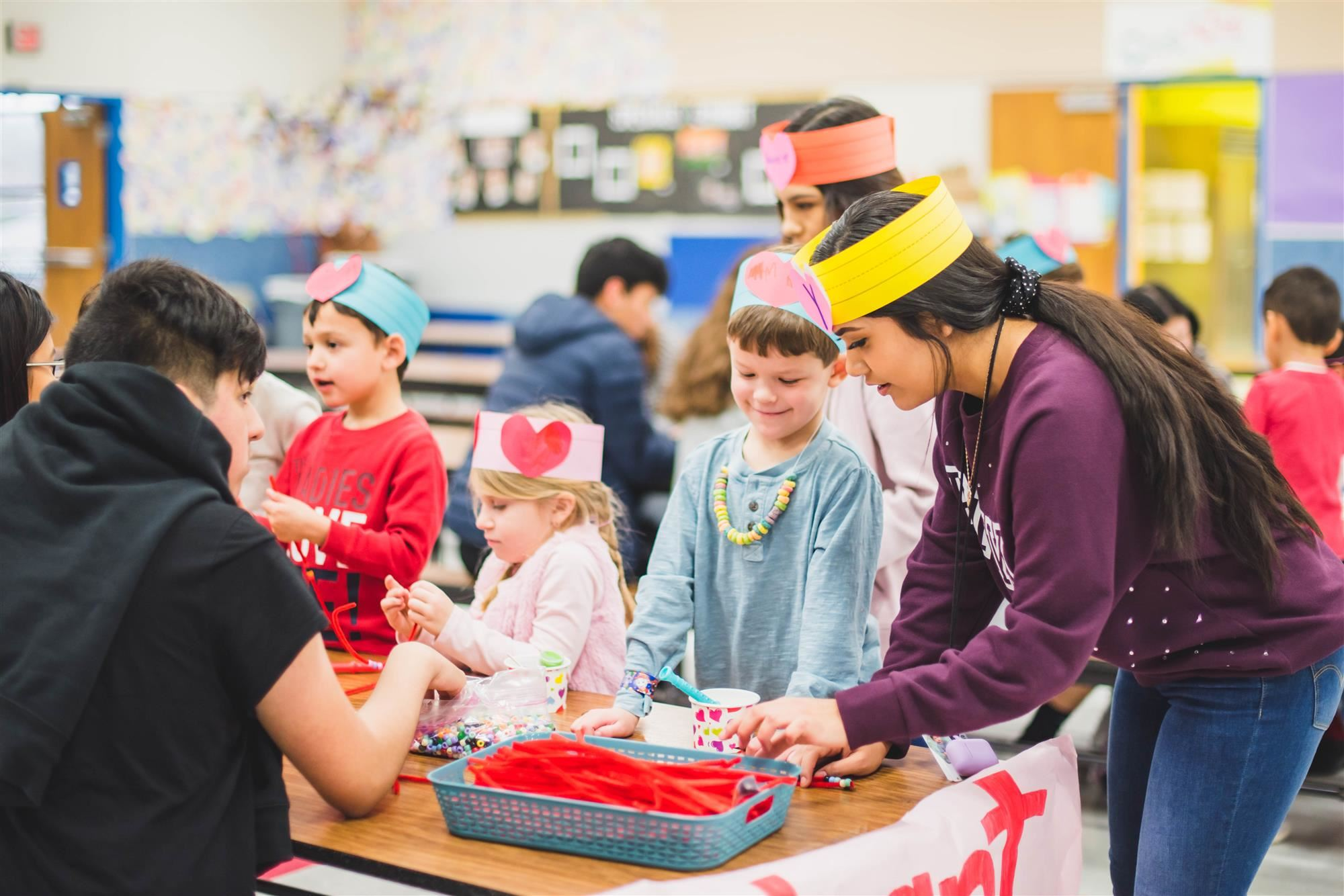 Younger students work with older students on valentine's day crafts