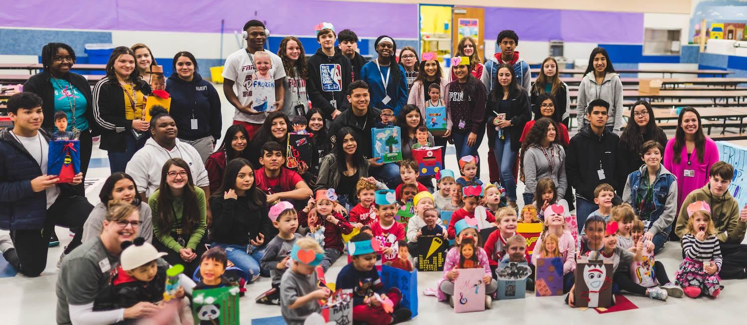 Group of high school and pre-k students pose with valentines' day boxes