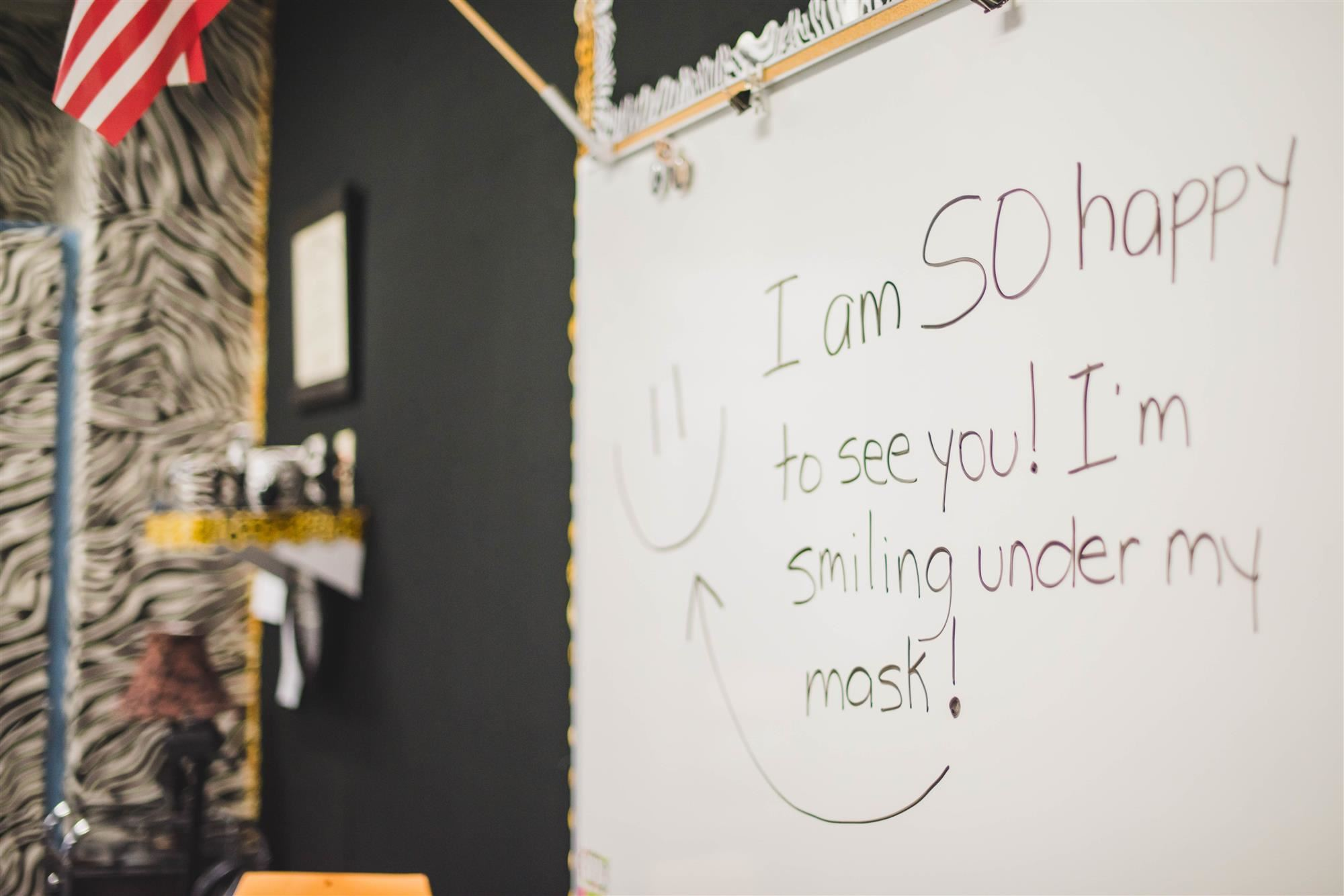 "Whiteboard has text ""I am SO happy to see you! I'm smiling under my mask!"""