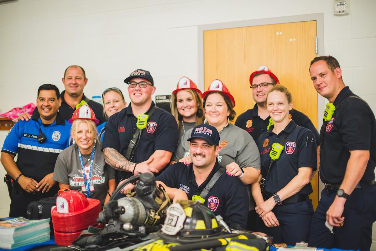 School staff, firefighters and police officer group smile together