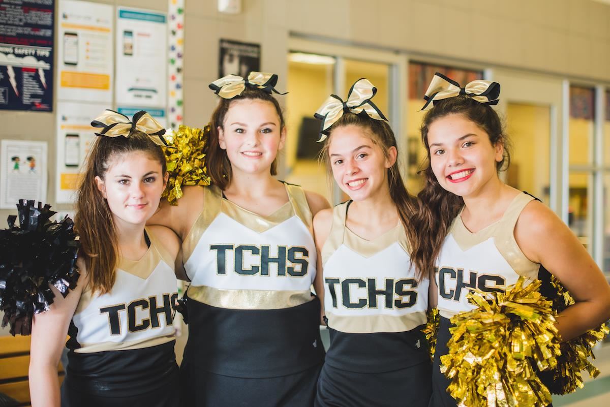 Four TCHS cheerleaders smile