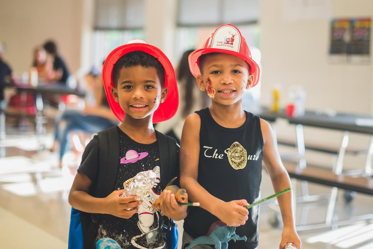 Two students smile wearing firefighter hats