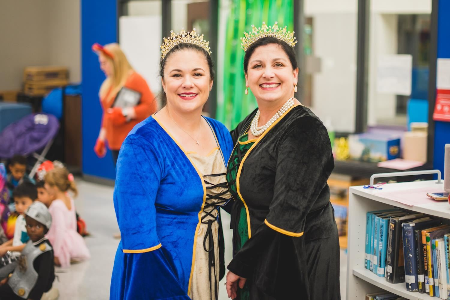 Polser principal and assistant principal smile in queen costumes