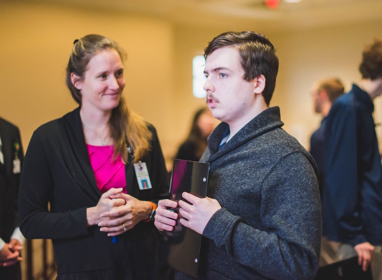student and teacher talk to potential employee at job fair