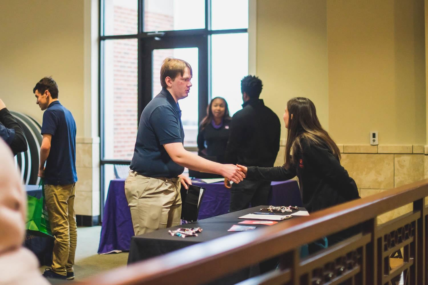 student shakes hands with potential employer at job fair