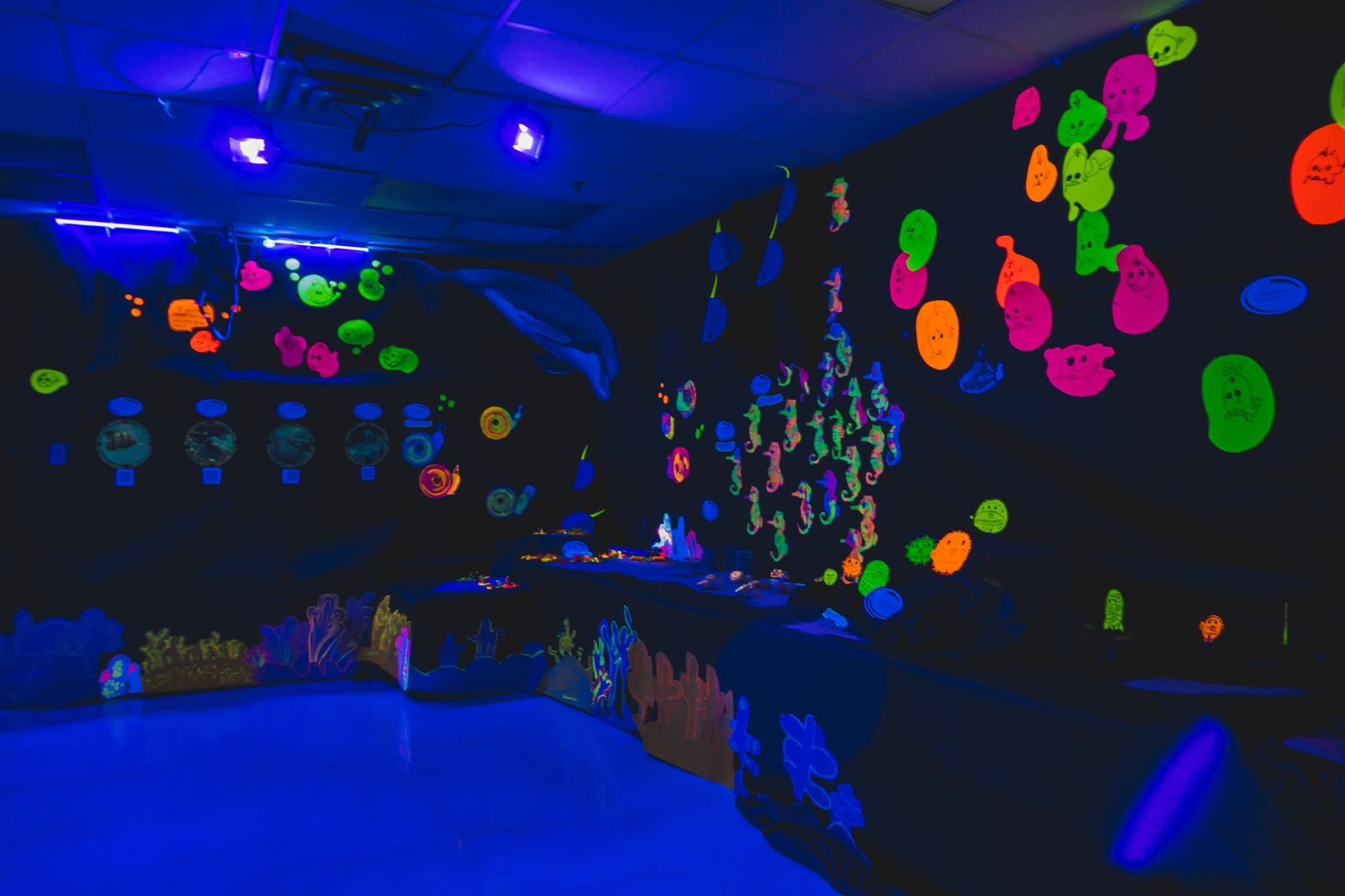 Imaginarium room with black lights and glowing artwork