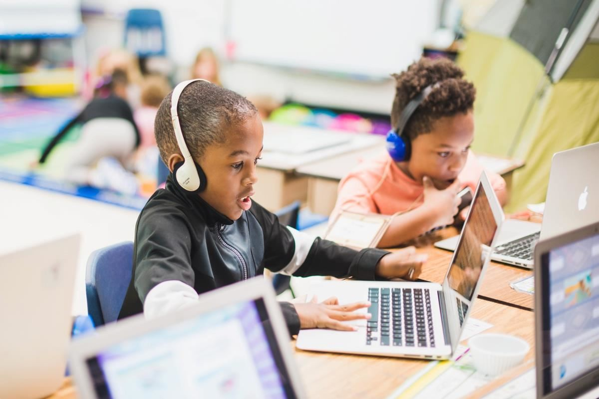 students learn at computers with headphones on their ears