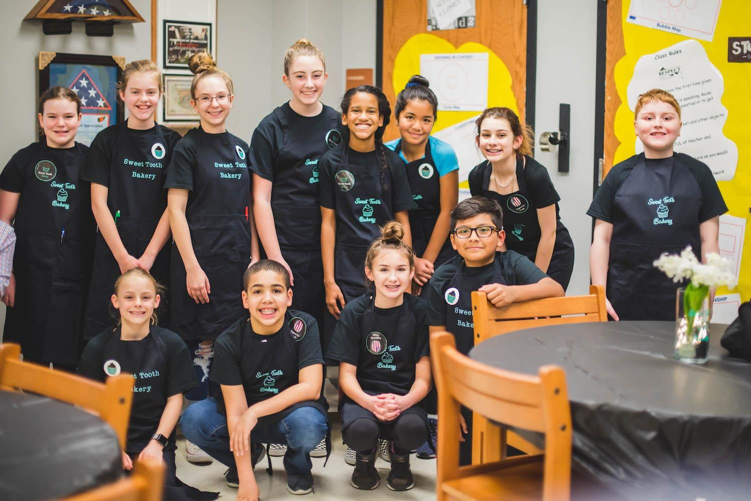 group of students in aprons smile together