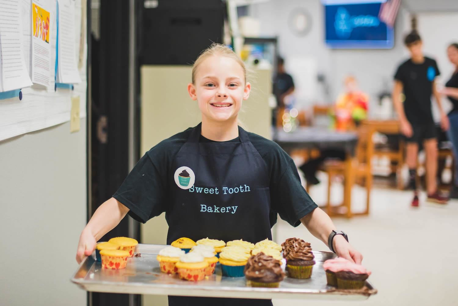 Student serves cupcakes on large pan