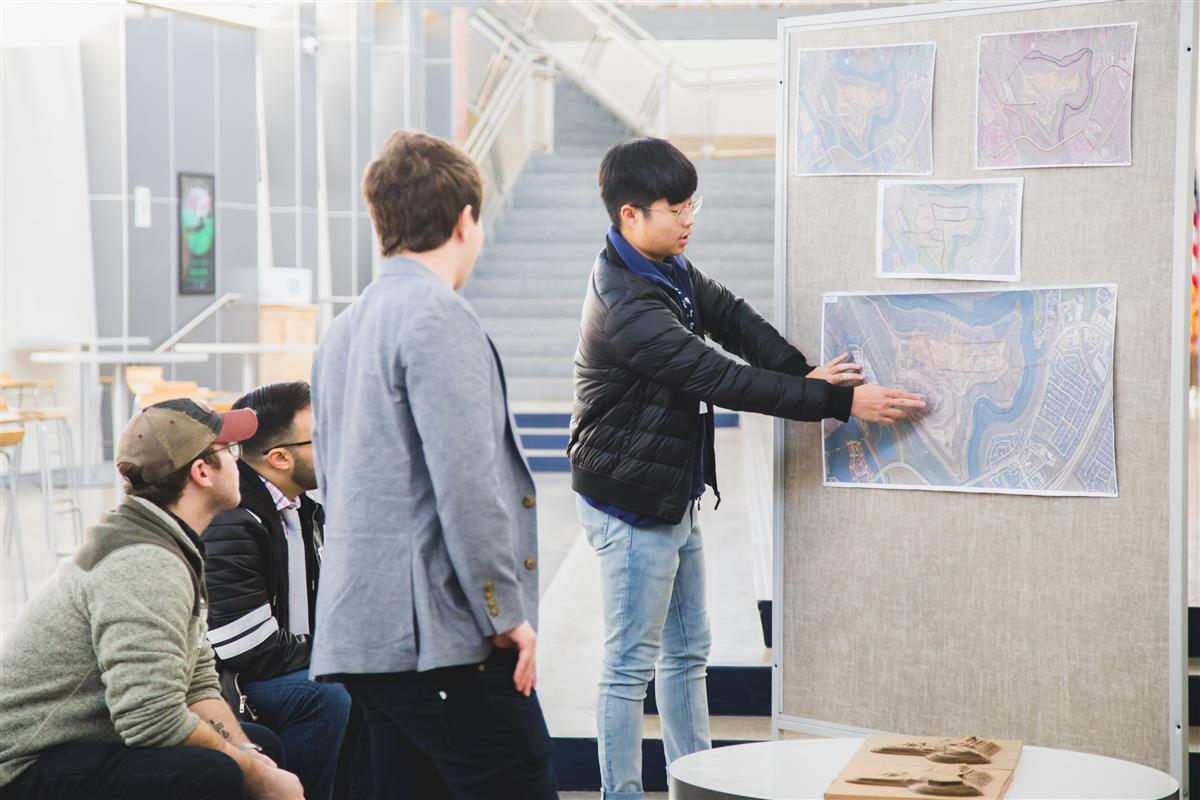 Architecture student presents project to professionals.