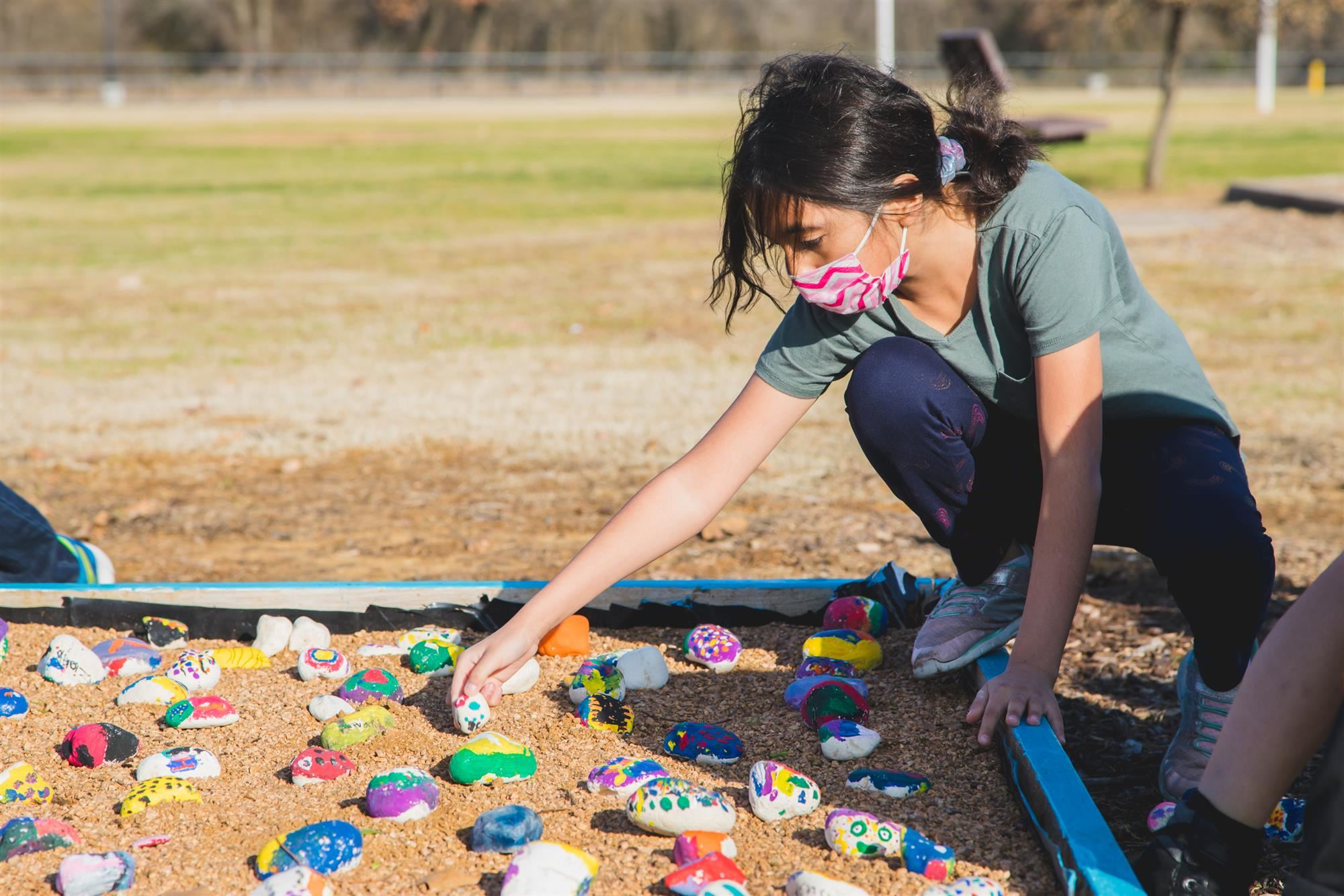 Vickery student places a rock in the garden bed.