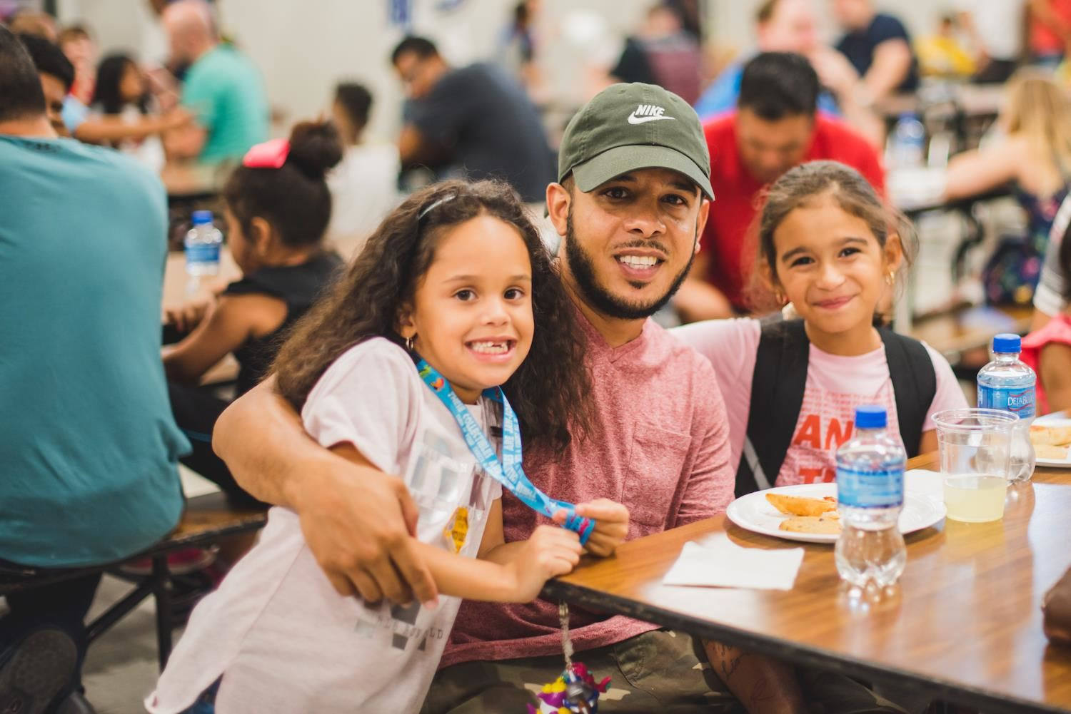 A parent and two students smile in cafeteria