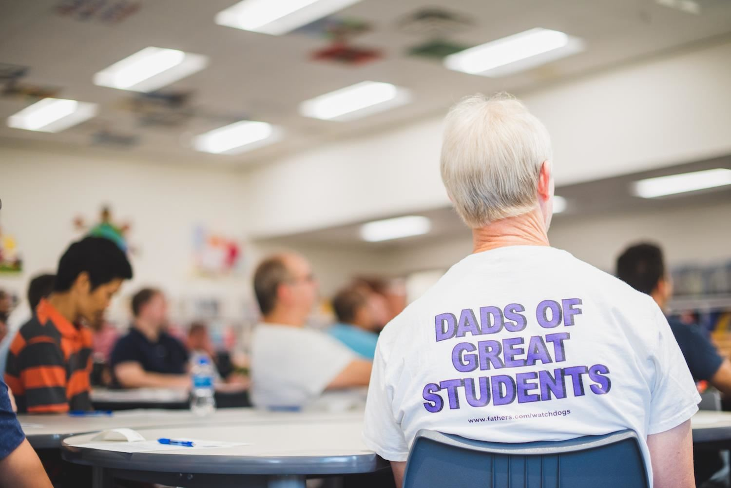 "Man's shirt reads, ""Dads of Great Students"""