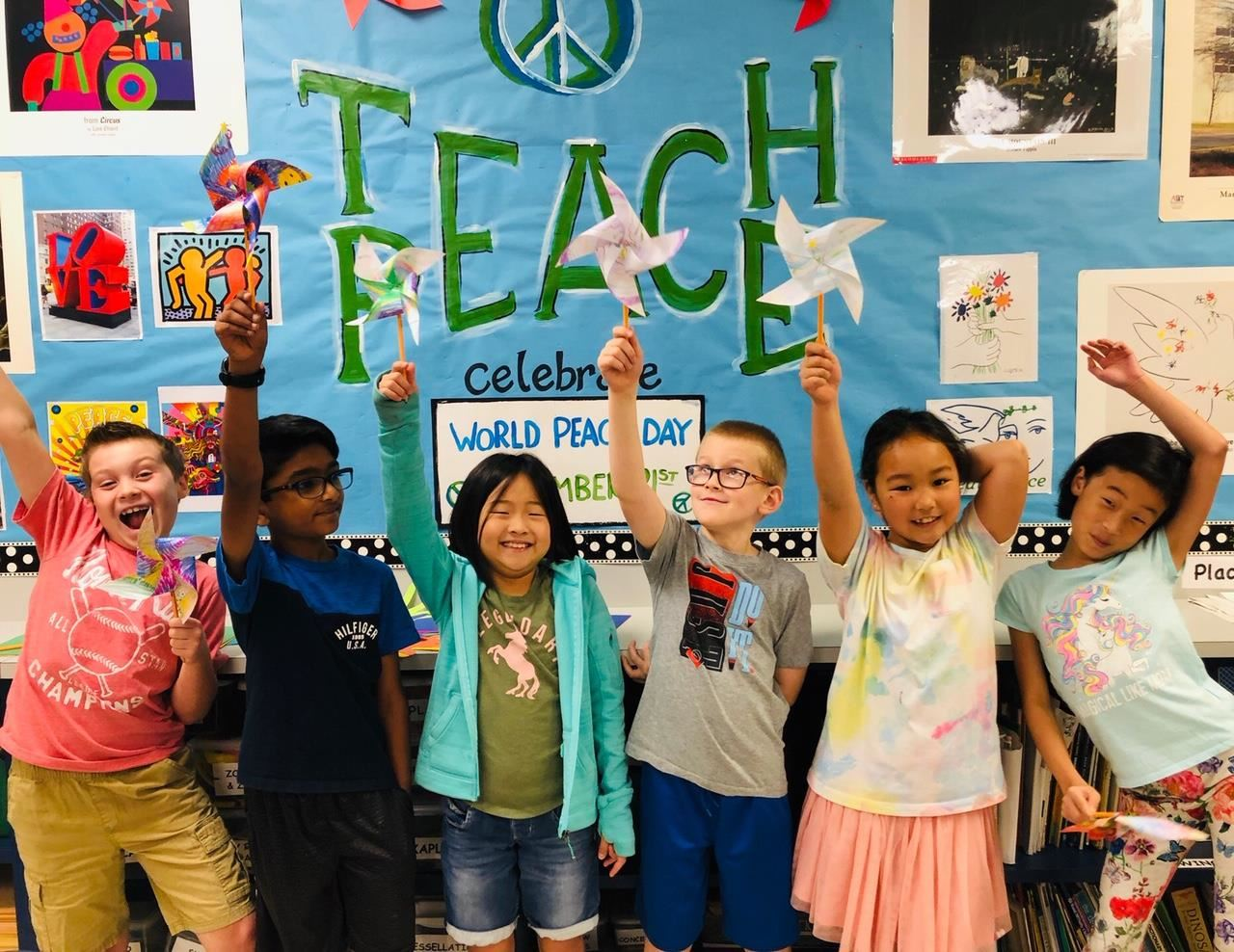 Bluebonnet students hold up their pinwheels in front of teach peace sign in the school. 2019
